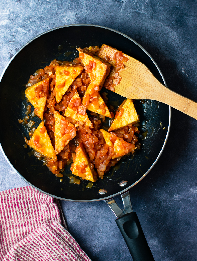tofu triangles coated in ketchup & onion sauce in fry pan