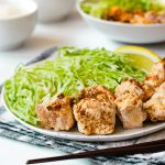 tofu karaage made in air fryer, served on plate with shredded cabbage and lemon wedge