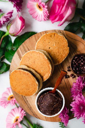 three vegan dorayaki overlapping each other on serving platter, flowers surrounding in background