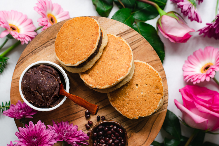 three vegan dorayaki viewed from above, overlapping each other on serving platter, flowers surrounding in background