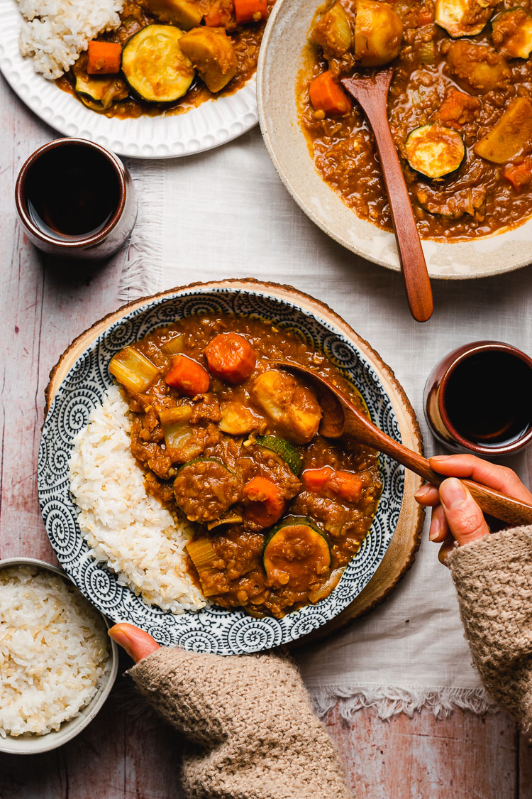 hands reaching for a bowl of vegan japanese curry with rice