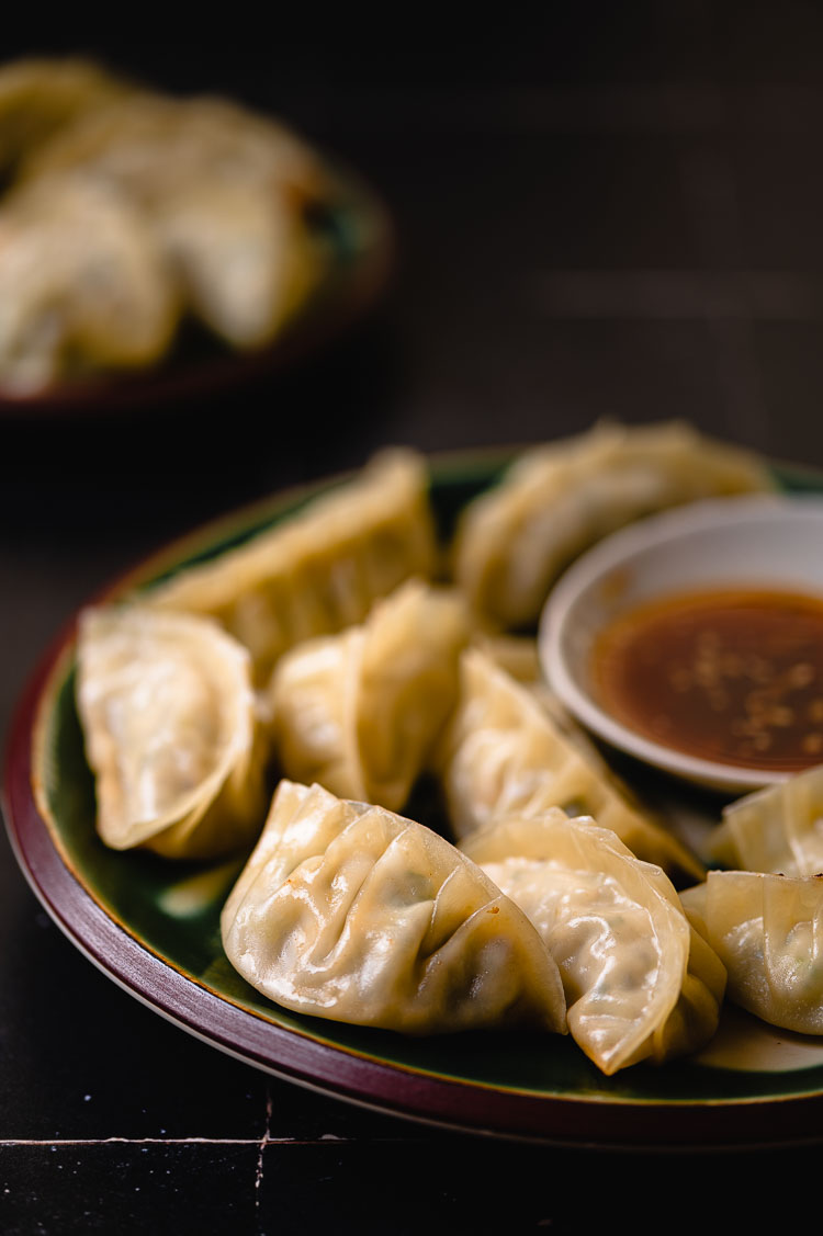 plate of gyoza with dipping sauce, second plate of gyoza in background