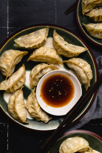 tofu gyoza on a plate with dipping sauce