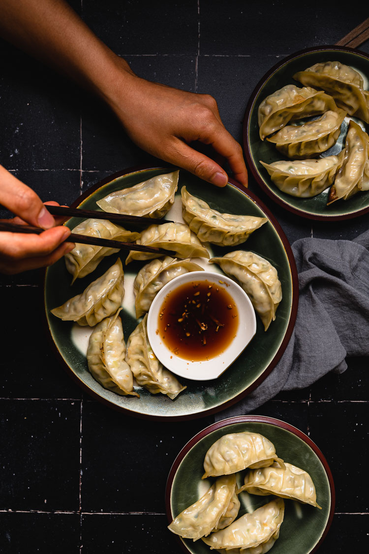 plate of gyoza with hands holding chopsticks reaching for a gyoza