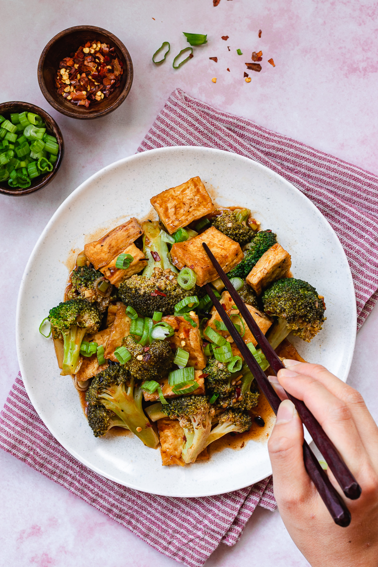 chili sauce tofu and broccoli served on a plate, hand holding chopsticks reaching for a piece of tofu