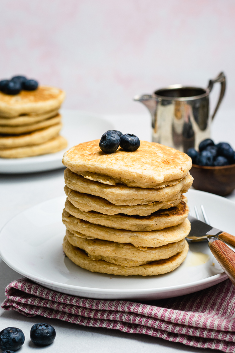 vegan oatmeal pancakes stacked on a plate with blueberries and another stack in the background
