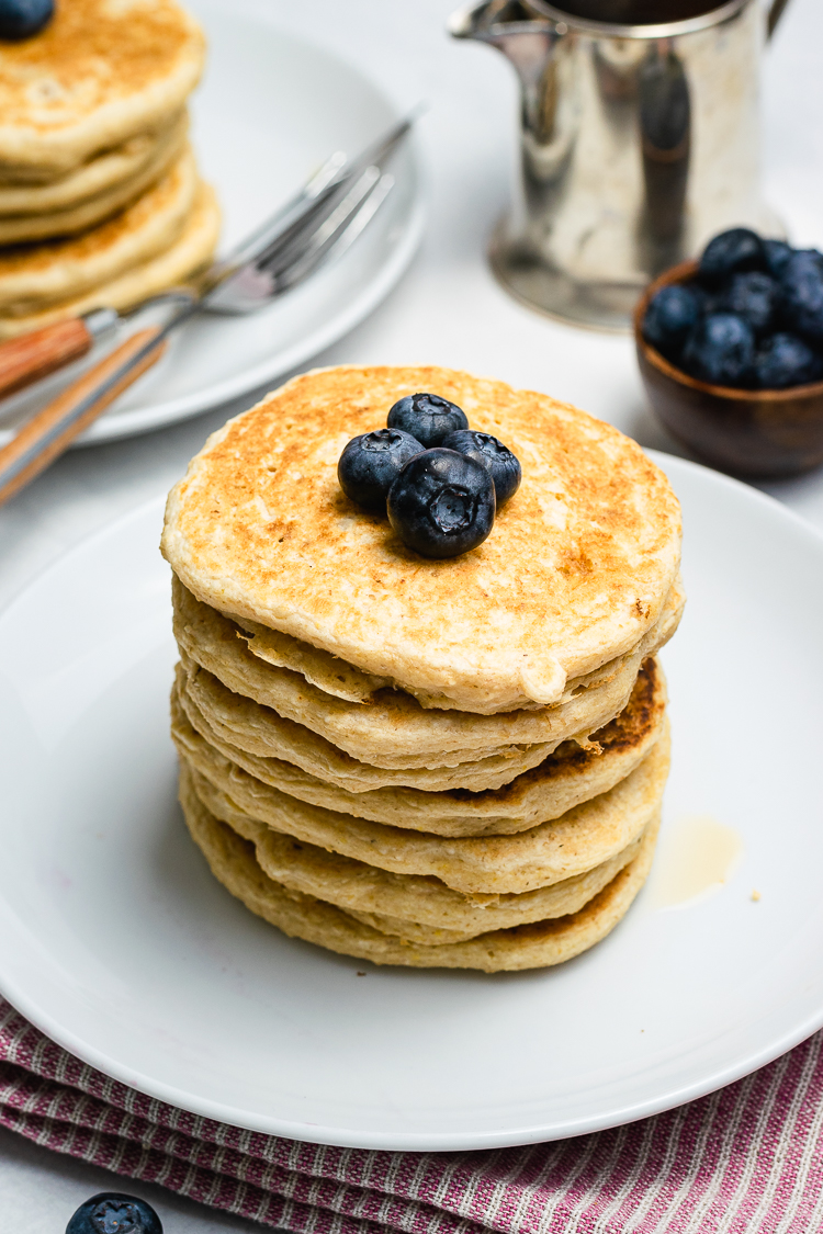 oatmeal pancakes stacked on a plate and topped with blueberries
