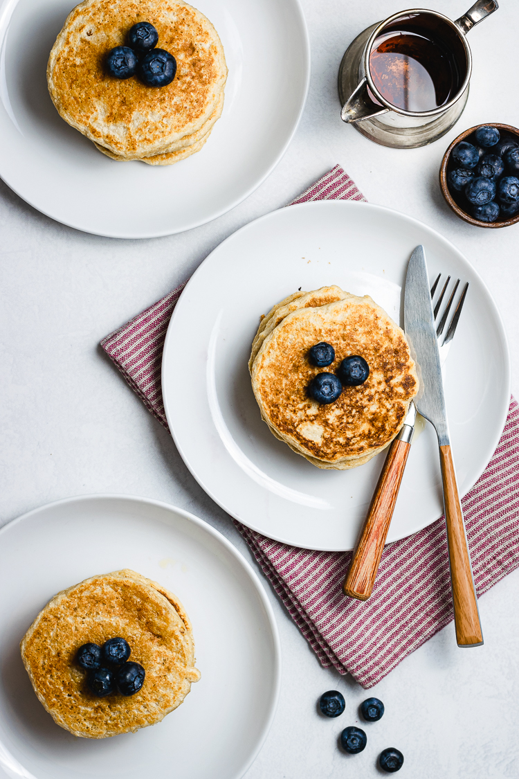 flatlay of stacked oatmeal pancakes on 3 different plates