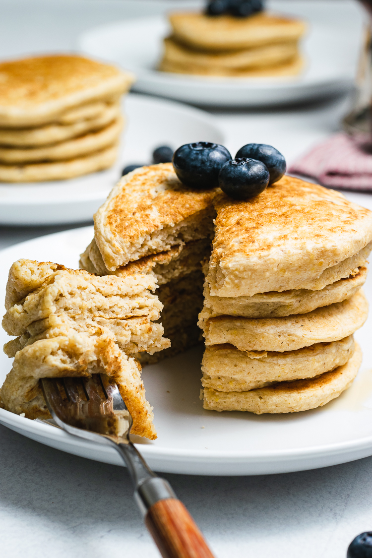 stack of oatmeal pancakes cut into with a fork