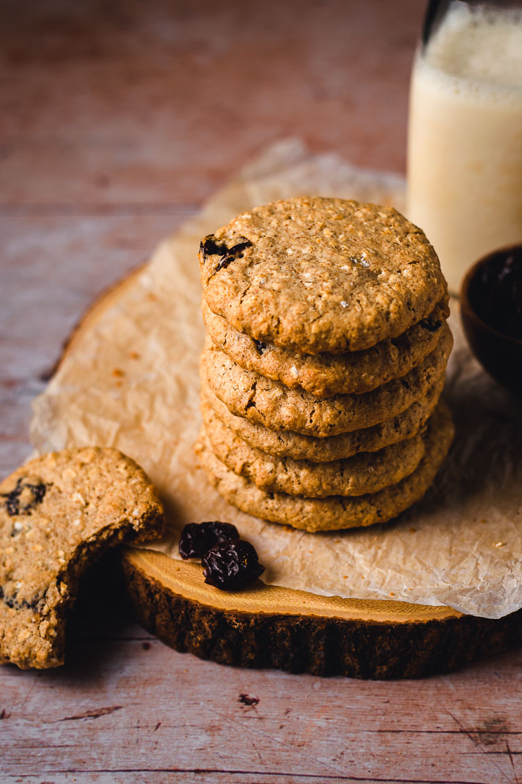 stack of chewy oatmeal raisin cookies with a bite taken out of one cookie on the side