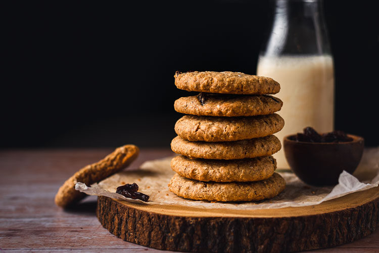 stack of oatmeal raisin cookies on a platter with milk