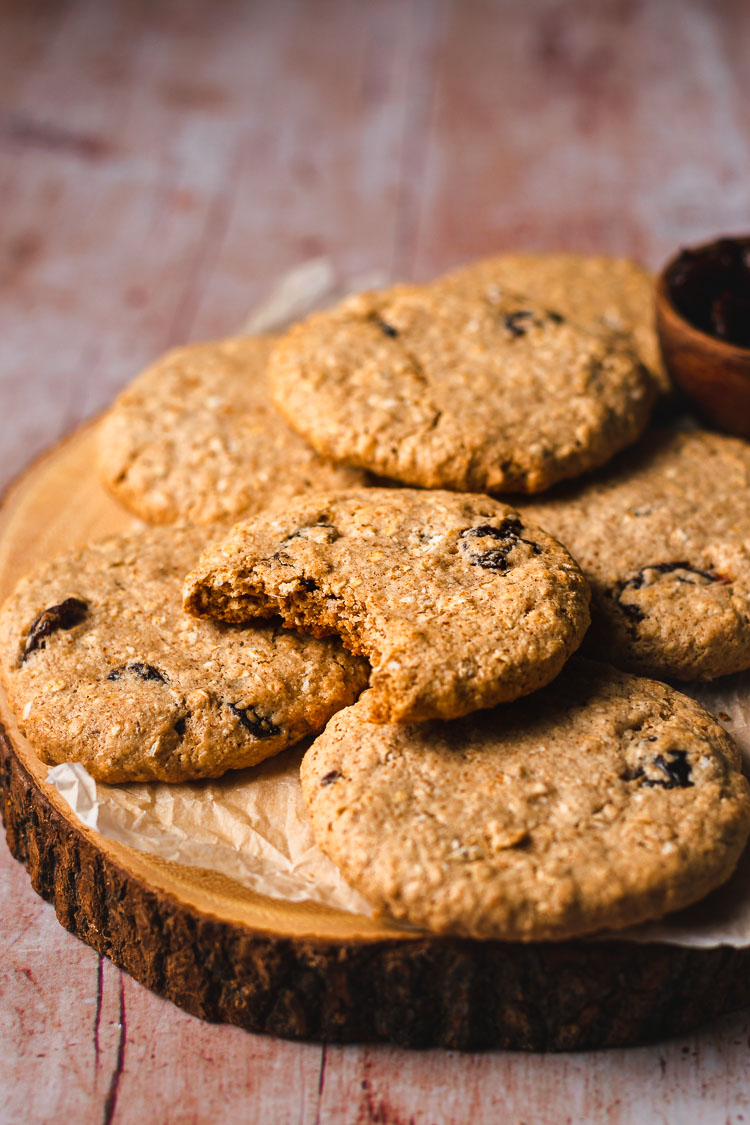 vegan oatmeal raisin cookies on a platter with a bite taken out of one