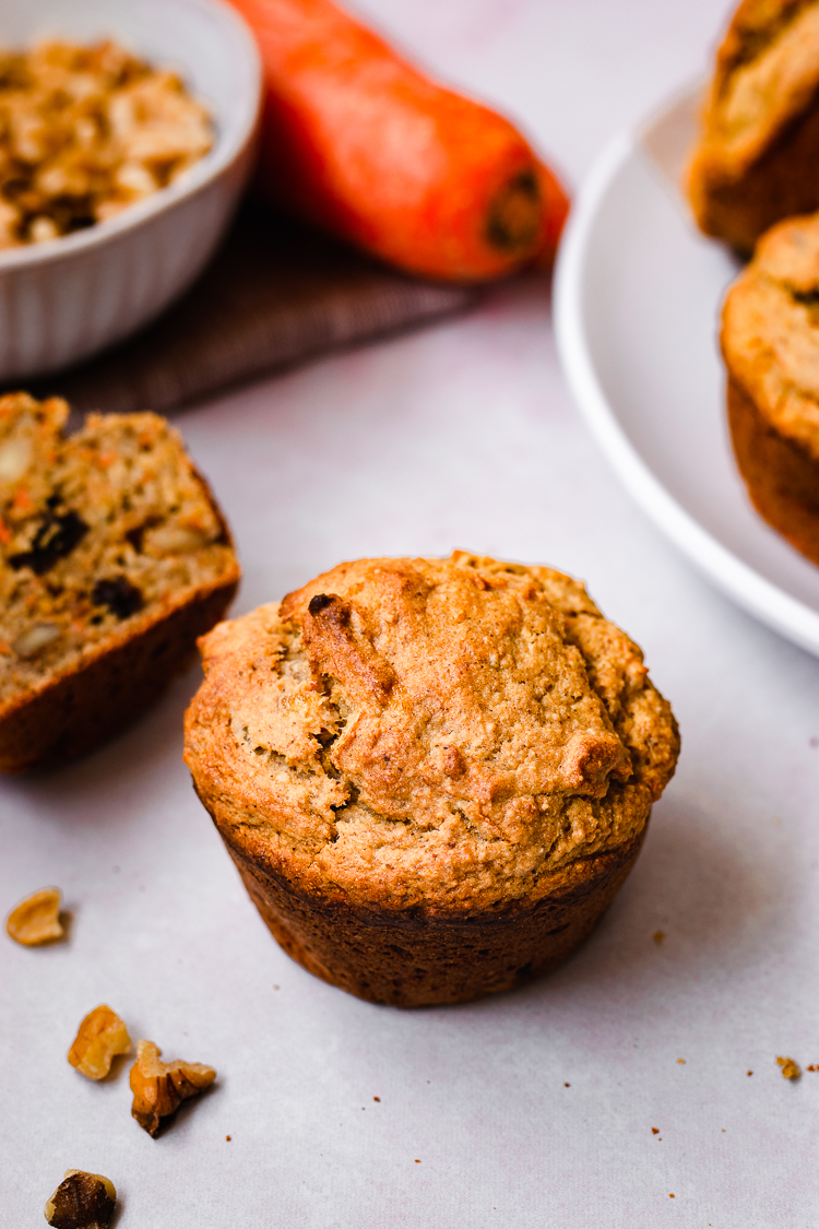 a vegan carrot banana muffin surrounded by muffins, walnuts, and carrots in the background