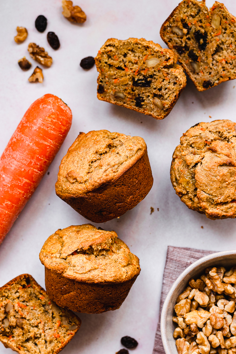 flatlay of vegan carrot banana muffins with carrot, walnuts, and raisins