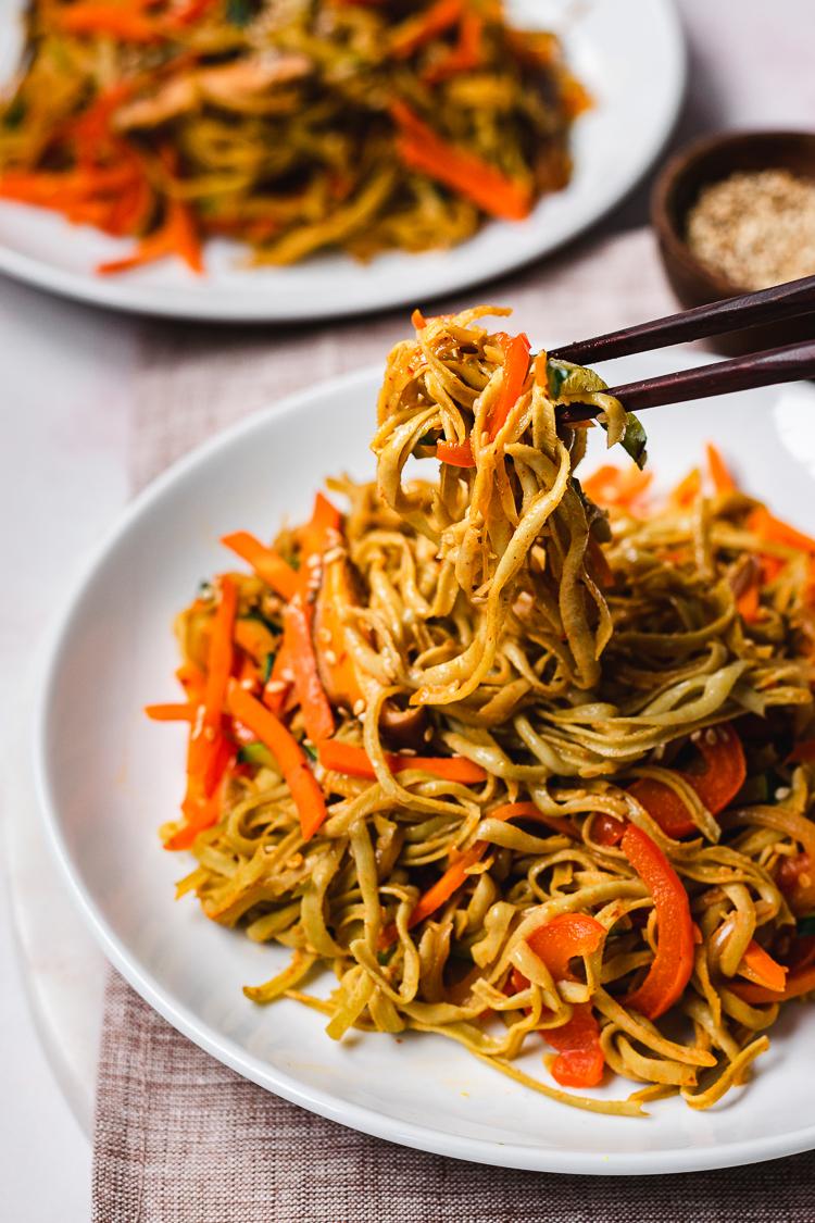 chopsticks holding a bite of edamame noodle stir fry above plate