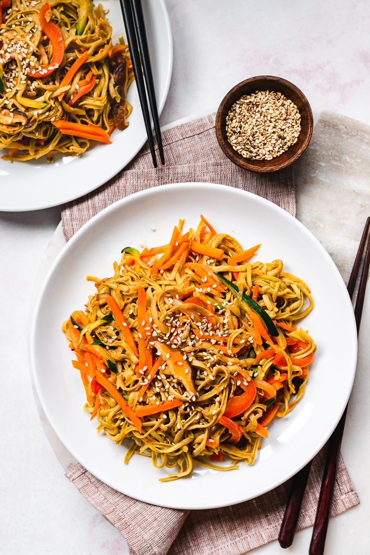 two plates of edamame noodle stir fry with a small bowl of sesame seeds