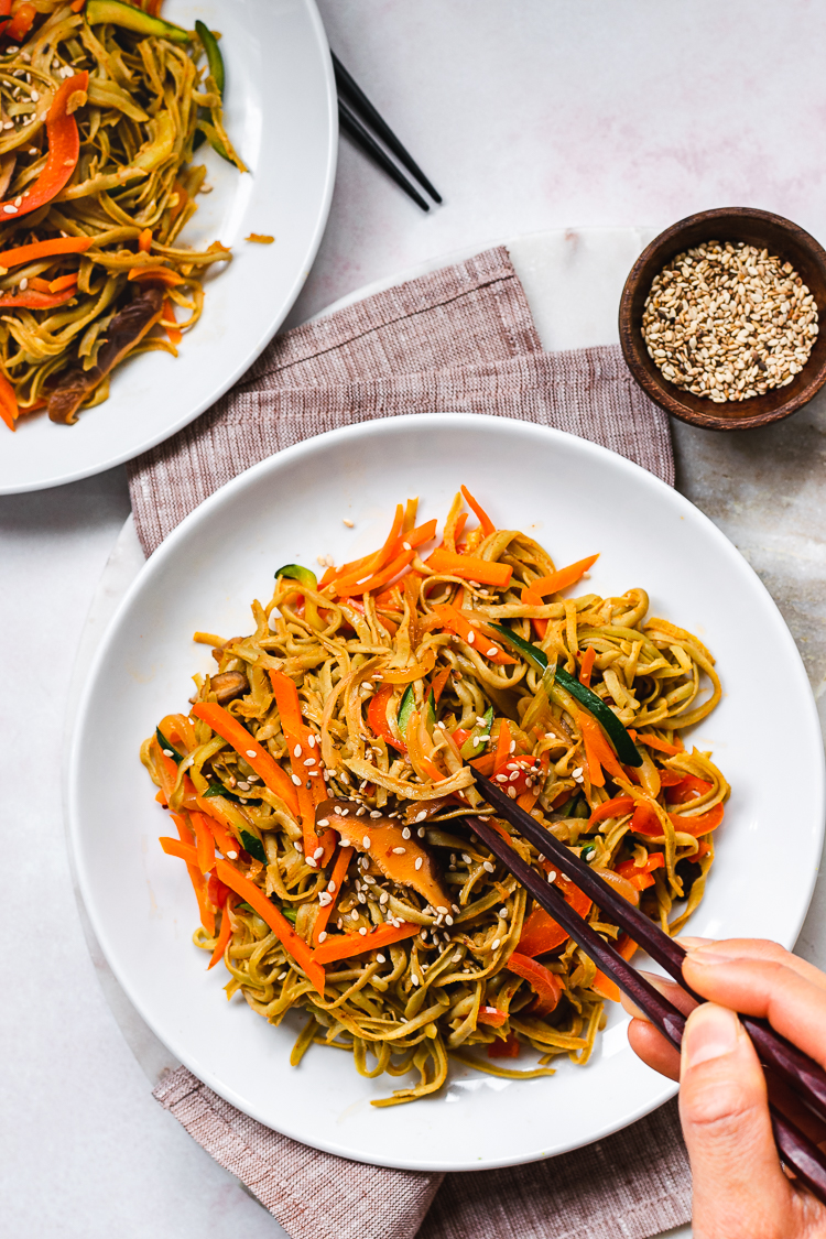 two plates of edamame noodle stir fry with hands on chopsticks reaching for the noodles