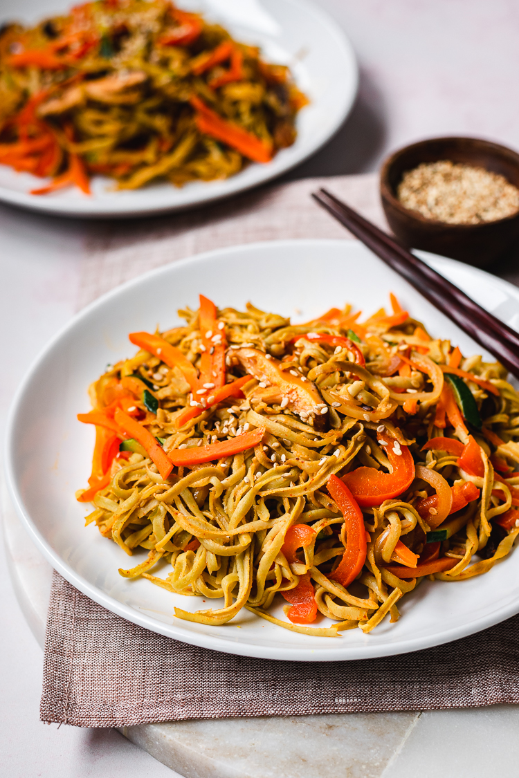 a plate of edamame noodle stir fry with another plate in the background