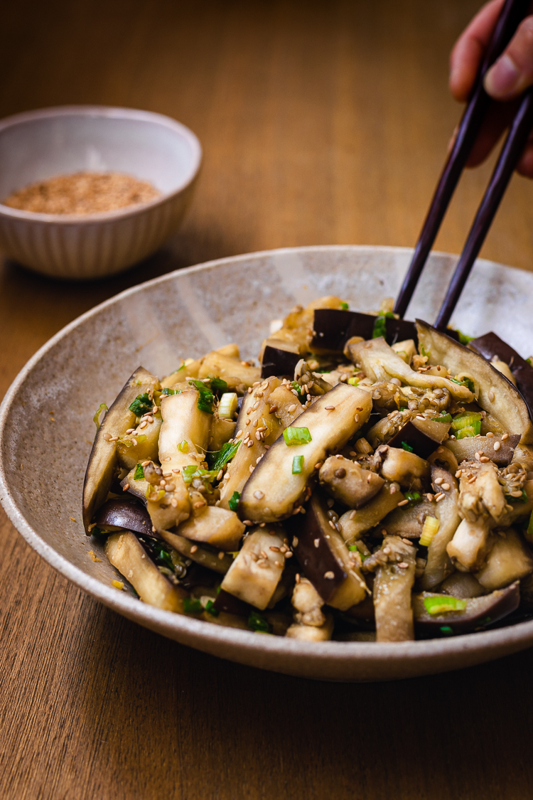 chopsticks in hand reaching for a piece of steamed eggplant in bowl