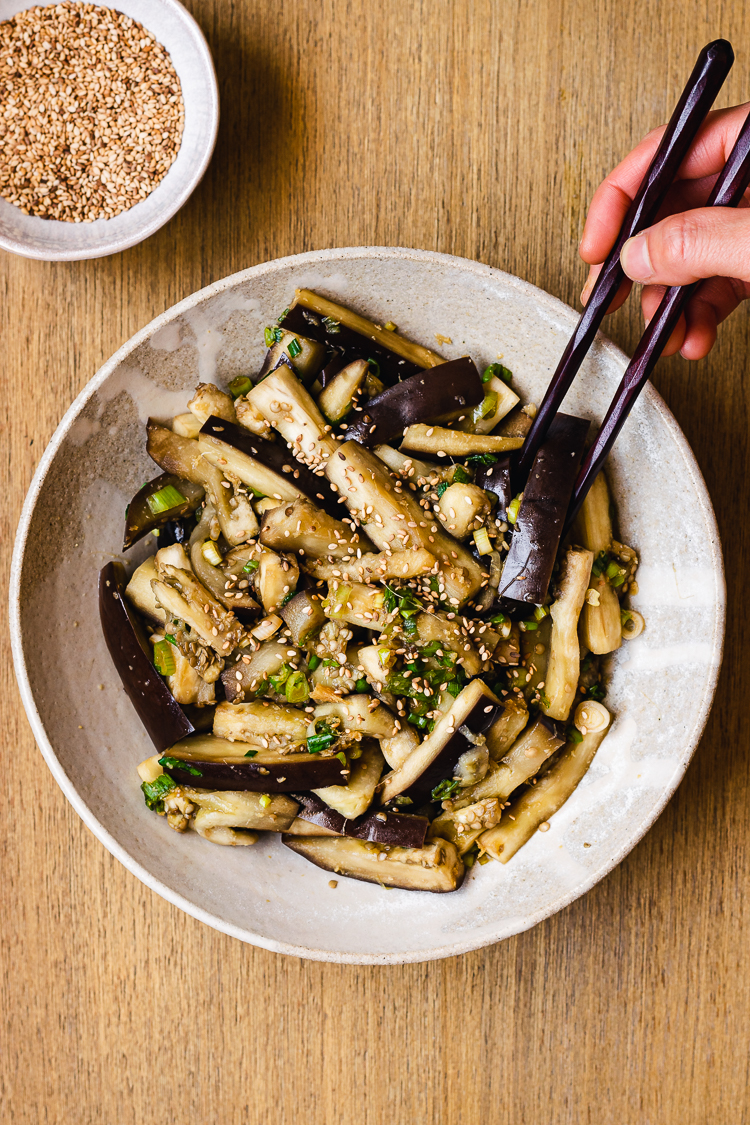 chopsticks in hand reaching for a piece of steamed eggplant on a plate