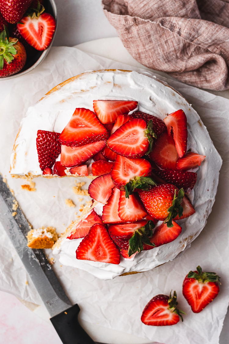 overhead shot of vegan strawberries and cream cake with a slice cut out