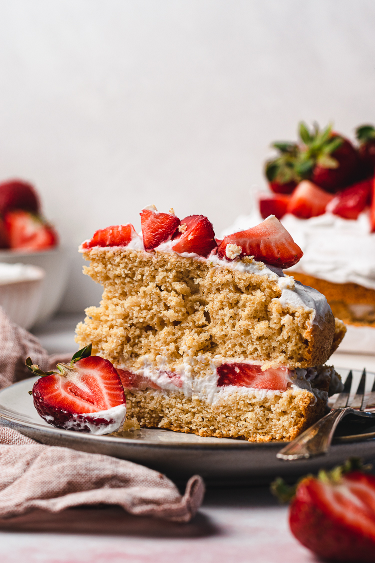 a slice of vegan strawberries and cream cake on a plate