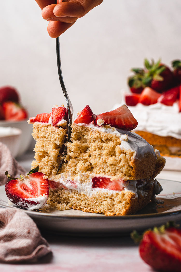 a slice of vegan strawberries and cream cake with a fork in hand slicing into it