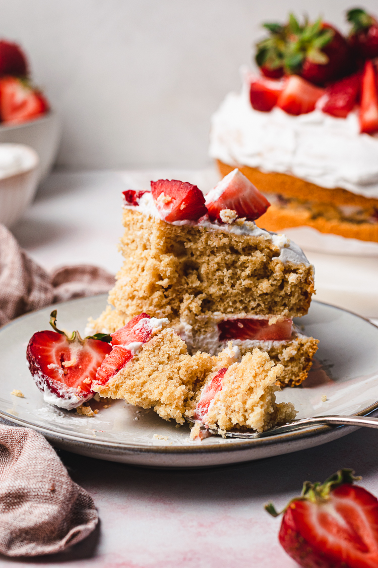 a slice of vegan strawberries and cream cake with a piece of the cake on a fork on the plate