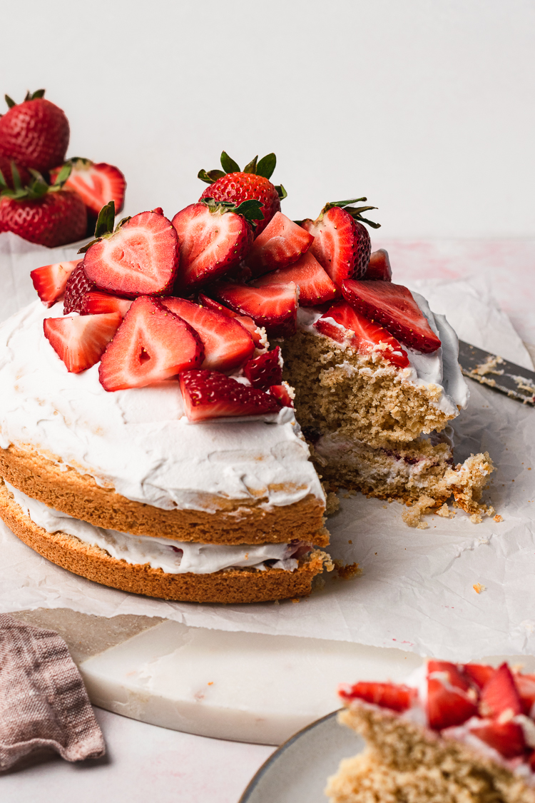 vegan strawberries and cream cake with a slice cut out