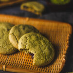 vegan matcha chocolate chip cookies arranged on a platter with a bite taken out of the cookie in front