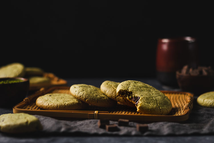 vegan matcha chocolate chunk cookies arranged on a serving platter with a bite taken out of one