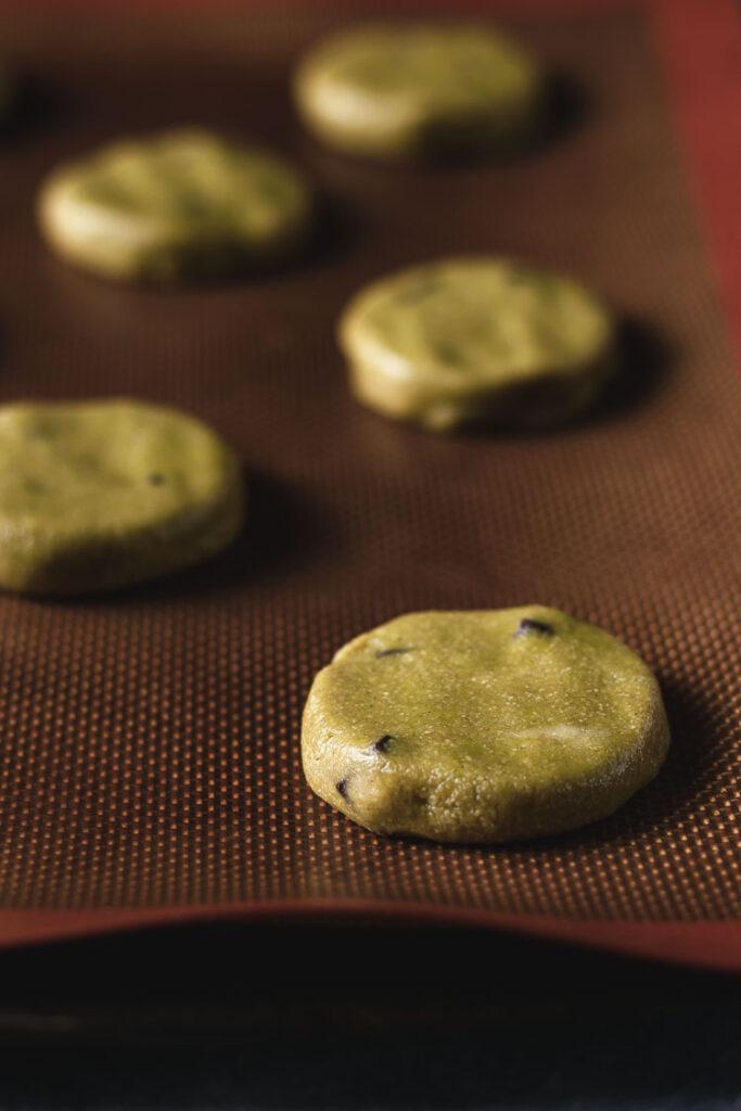vegan matcha cookie dough discs on baking sheet before baking