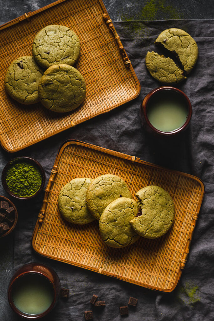 vegan matcha cookies arranged on serving platters with hot matcha tea on the side