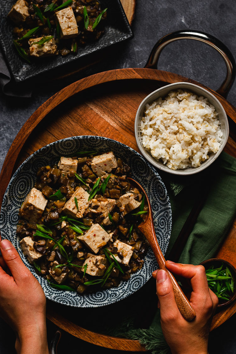 a bowl of vegan mapo tofu with hands holding a spoonful of tofu
