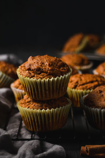 vegan pumpkin muffins stacked on top of each other, set on a wire rack