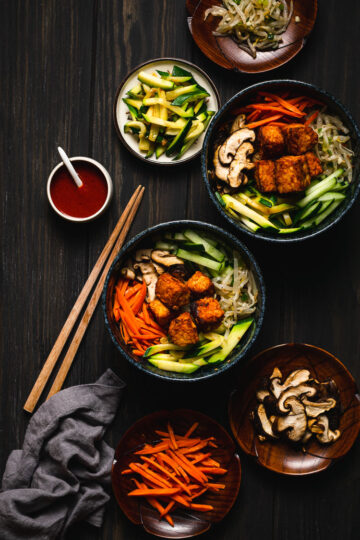 two bowls of tempeh bibimbap with fillings on the side