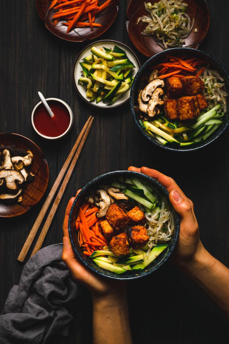 hands holding a bowl of tempeh bibimbap