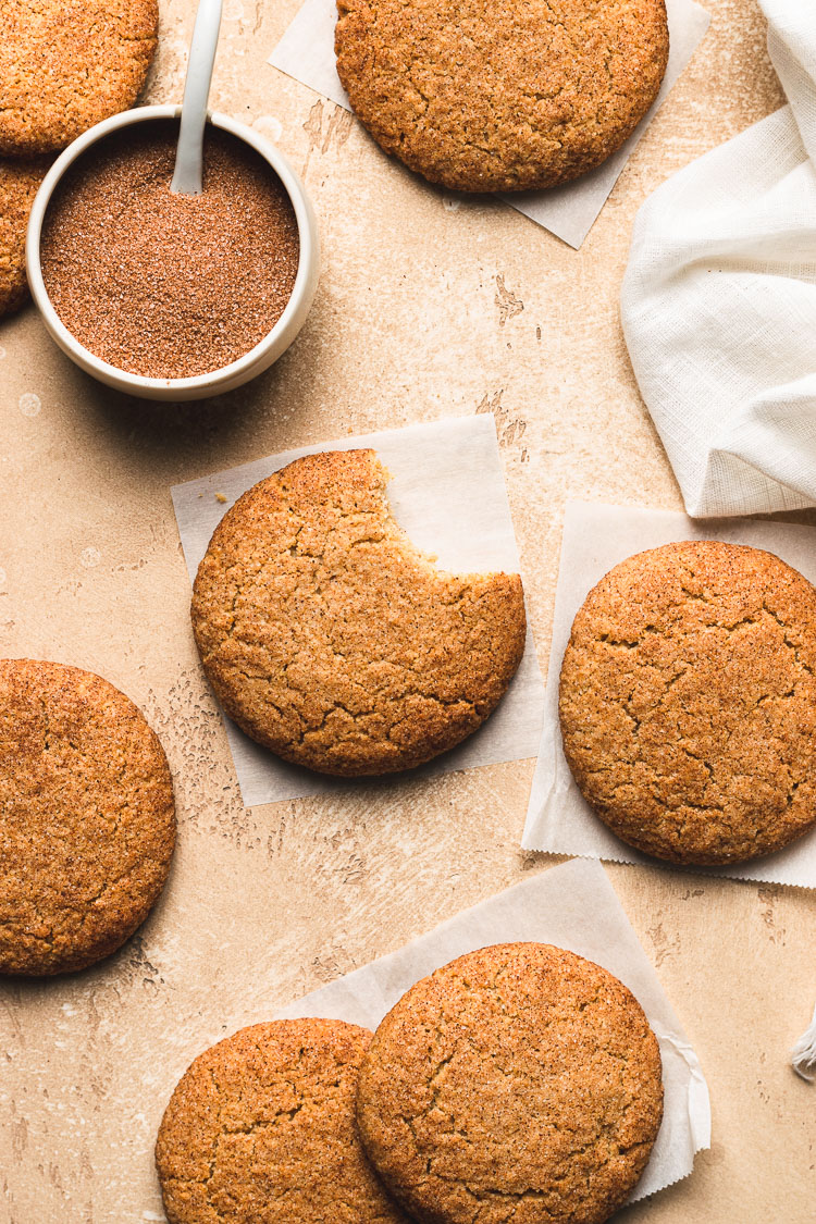 vegan gluten free snickerdoodle flatlay with a bite taken out of one cookie