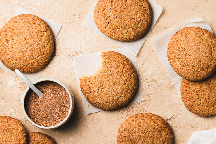 vegan gluten free snickerdoodle with a bite taken out of it, surrounded by more snickerdoodles