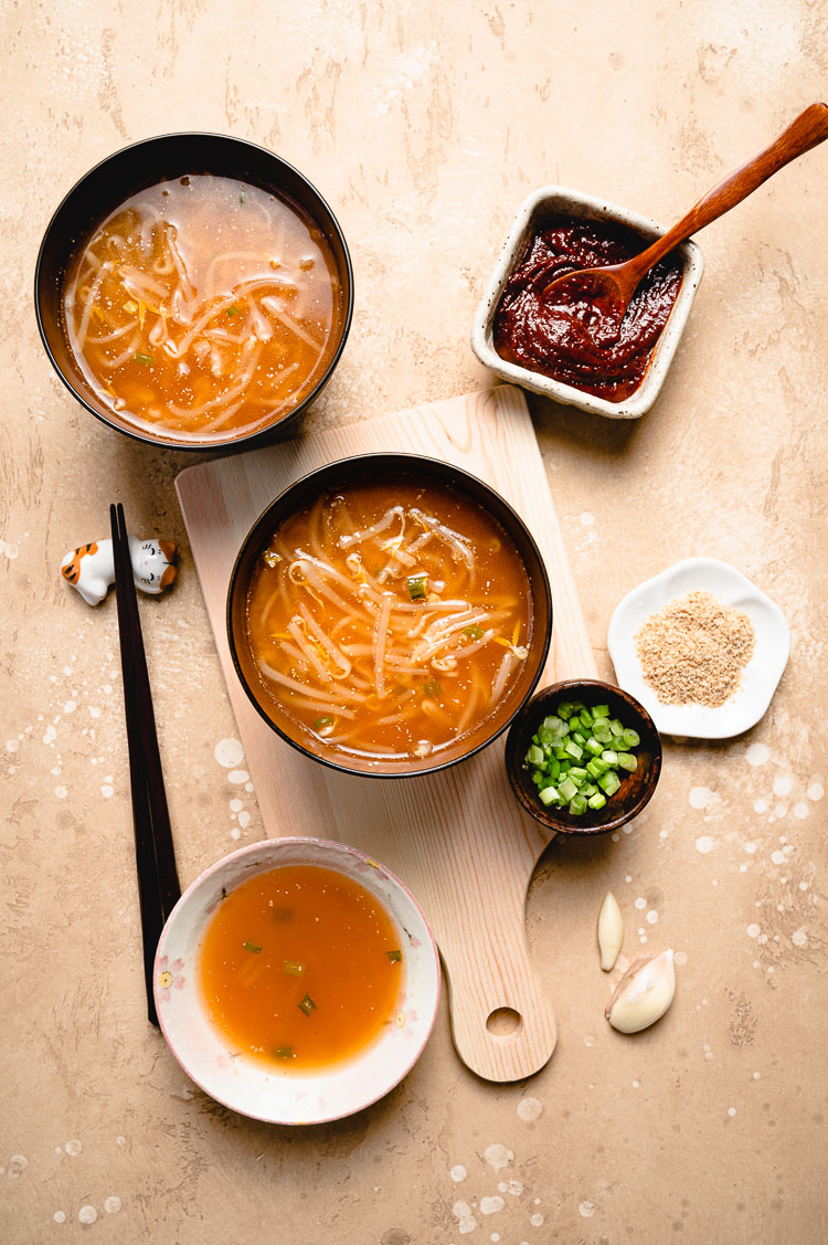 flatlay of 3 bowls of spicy bean sprout miso soup with ingredient bowls on the side