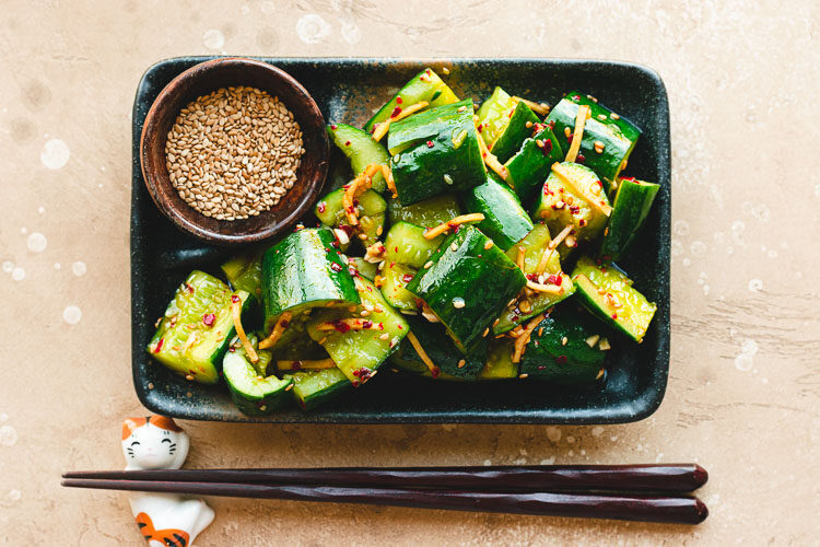 japanese smashed cucumbers on a plate with a pinch bowl of sesame seeds
